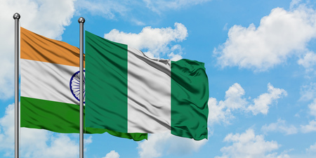 India and Nigeria flag waving in the wind against white cloudy blue sky together. Diplomacy concept, international relations. 스톡 콘텐츠