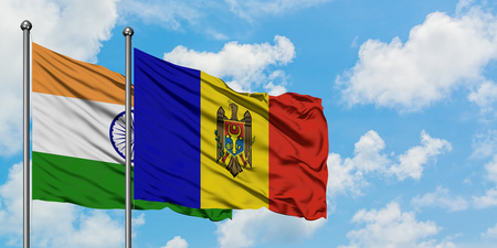 India and Moldova flag waving in the wind against white cloudy blue sky together. Diplomacy concept, international relations.