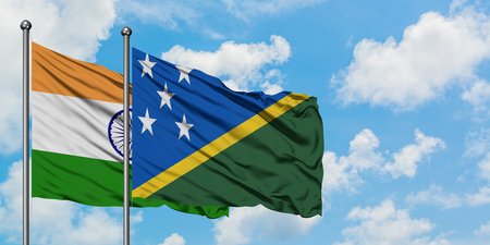 India and Solomon Islands flag waving in the wind against white cloudy blue sky together. Diplomacy concept, international relations.