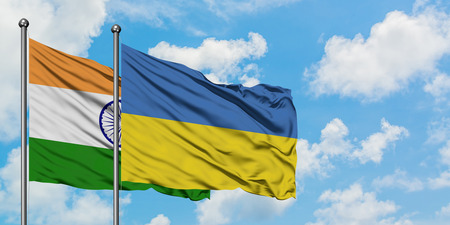 India and Ukraine flag waving in the wind against white cloudy blue sky together. Diplomacy concept, international relations.