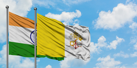 India and Vatican City flag waving in the wind against white cloudy blue sky together. Diplomacy concept, international relations.