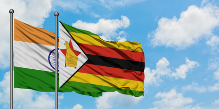 India and Zimbabwe flag waving in the wind against white cloudy blue sky together. Diplomacy concept, international relations. Stock Photo