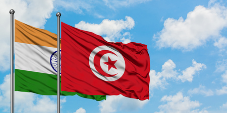 India and Tunisia flag waving in the wind against white cloudy blue sky together. Diplomacy concept, international relations. Stock Photo