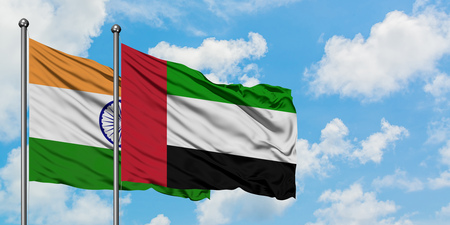 India and United Arab Emirates flag waving in the wind against white cloudy blue sky together. Diplomacy concept, international relations.