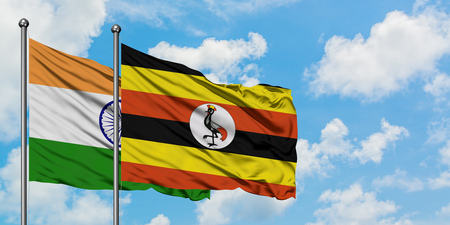 India and Uganda flag waving in the wind against white cloudy blue sky together. Diplomacy concept, international relations.