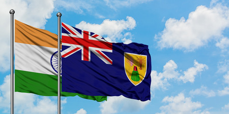 India and Turks And Caicos Islands flag waving in the wind against white cloudy blue sky together. Diplomacy concept, international relations. Stock Photo