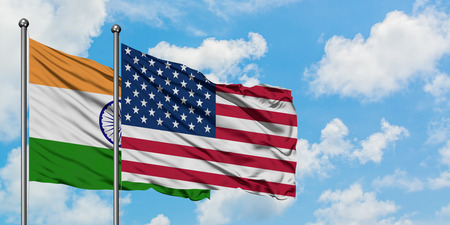India and United States flag waving in the wind against white cloudy blue sky together. Diplomacy concept, international relations.