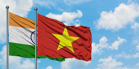 India and Vietnam flag waving in the wind against white cloudy blue sky together. Diplomacy concept, international relations.