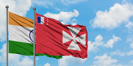 India and Wallis And Futuna flag waving in the wind against white cloudy blue sky together. Diplomacy concept, international relations.