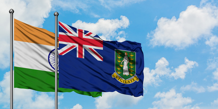 India and British Virgin Islands flag waving in the wind against white cloudy blue sky together. Diplomacy concept, international relations. Stock Photo