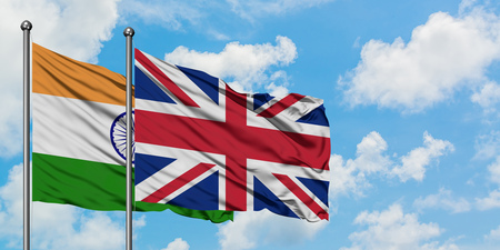 India and United Kingdom flag waving in the wind against white cloudy blue sky together. Diplomacy concept, international relations.