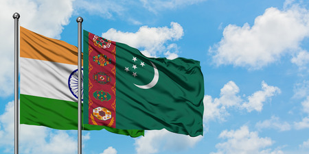 India and Turkmenistan flag waving in the wind against white cloudy blue sky together. Diplomacy concept, international relations. Stock Photo