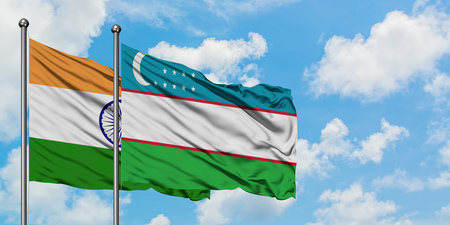 India and Uzbekistan flag waving in the wind against white cloudy blue sky together. Diplomacy concept, international relations. Stock Photo
