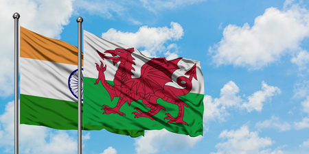 India and Wales flag waving in the wind against white cloudy blue sky together. Diplomacy concept, international relations.