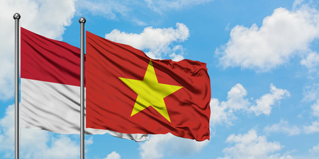 Iraq and Vietnam flag waving in the wind against white cloudy blue sky together. Diplomacy concept, international relations.