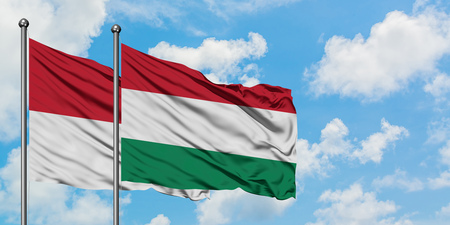 Iraq and Hungary flag waving in the wind against white cloudy blue sky together. Diplomacy concept, international relations.