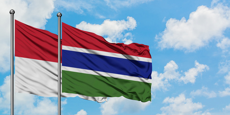 Iraq and Gambia flag waving in the wind against white cloudy blue sky together. Diplomacy concept, international relations.