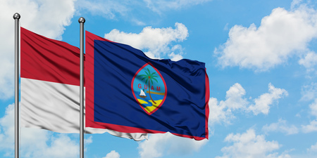 Iraq and Guam flag waving in the wind against white cloudy blue sky together. Diplomacy concept, international relations.