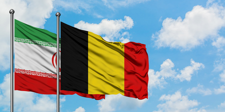 Iran and Belgium flag waving in the wind against white cloudy blue sky together. Diplomacy concept, international relations.