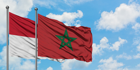 Iraq and Morocco flag waving in the wind against white cloudy blue sky together. Diplomacy concept, international relations. Stockfoto