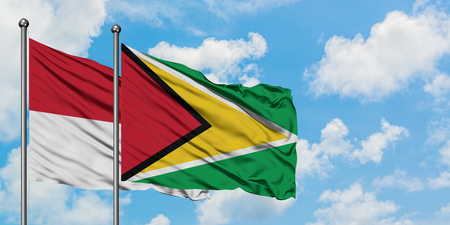 Iraq and Guyana flag waving in the wind against white cloudy blue sky together. Diplomacy concept, international relations.