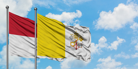 Iraq and Vatican City flag waving in the wind against white cloudy blue sky together. Diplomacy concept, international relations.