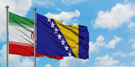Iran and Bosnia Herzegovina flag waving in the wind against white cloudy blue sky together. Diplomacy concept, international relations.