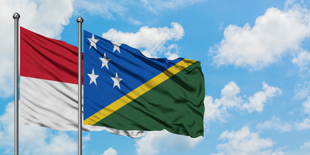 Iraq and Solomon Islands flag waving in the wind against white cloudy blue sky together. Diplomacy concept, international relations.