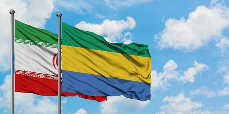 Iran and Gabon flag waving in the wind against white cloudy blue sky together. Diplomacy concept, international relations. 版權商用圖片
