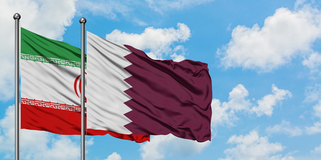 Iran and Qatar flag waving in the wind against white cloudy blue sky together. Diplomacy concept, international relations.