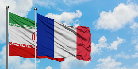 Iran and France flag waving in the wind against white cloudy blue sky together. Diplomacy concept, international relations.