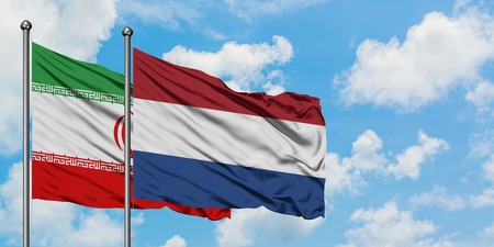 Iran and Netherlands flag waving in the wind against white cloudy blue sky together. Diplomacy concept, international relations.