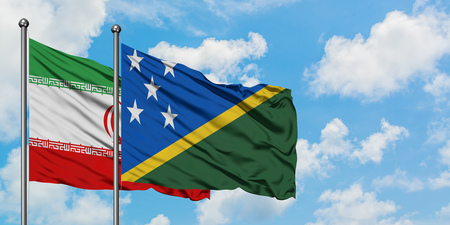 Iran and Solomon Islands flag waving in the wind against white cloudy blue sky together. Diplomacy concept, international relations.
