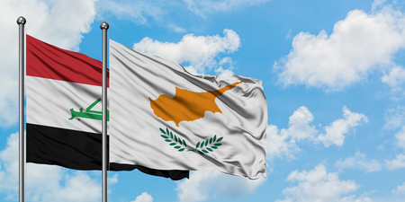 Iraq and Cyprus flag waving in the wind against white cloudy blue sky together. Diplomacy concept, international relations.
