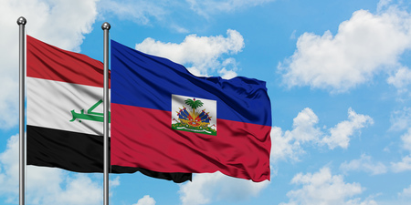 Iraq and Haiti flag waving in the wind against white cloudy blue sky together. Diplomacy concept, international relations. Stock Photo