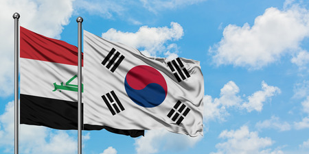 Iraq and South Korea flag waving in the wind against white cloudy blue sky together. Diplomacy concept, international relations.