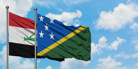Iraq and Solomon Islands flag waving in the wind against white cloudy blue sky together. Diplomacy concept, international relations. Stok Fotoğraf