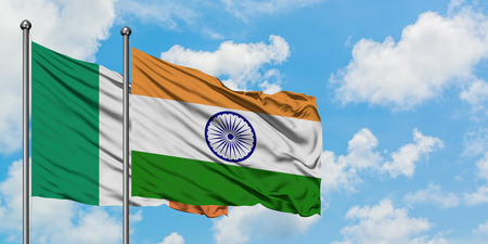 Ireland and India flag waving in the wind against white cloudy blue sky together. Diplomacy concept, international relations.