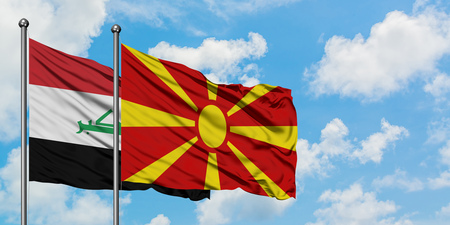 Iraq and Macedonia flag waving in the wind against white cloudy blue sky together. Diplomacy concept, international relations. Stockfoto