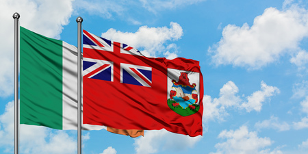 Ireland and Bermuda flag waving in the wind against white cloudy blue sky together. Diplomacy concept, international relations.