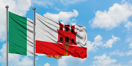 Ireland and Gibraltar flag waving in the wind against white cloudy blue sky together. Diplomacy concept, international relations. Stock Photo