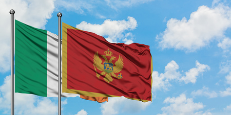 Ireland and Montenegro flag waving in the wind against white cloudy blue sky together. Diplomacy concept, international relations.