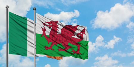 Ireland and Wales flag waving in the wind against white cloudy blue sky together. Diplomacy concept, international relations.