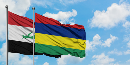 Iraq and Mauritius flag waving in the wind against white cloudy blue sky together. Diplomacy concept, international relations.