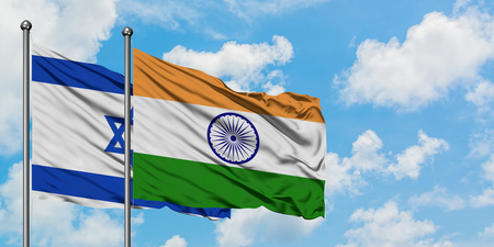 Israel and India flag waving in the wind against white cloudy blue sky together. Diplomacy concept, international relations.