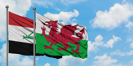 Iraq and Wales flag waving in the wind against white cloudy blue sky together. Diplomacy concept, international relations.