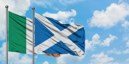 Ireland and Scotland flag waving in the wind against white cloudy blue sky together. Diplomacy concept, international relations. Stock Photo