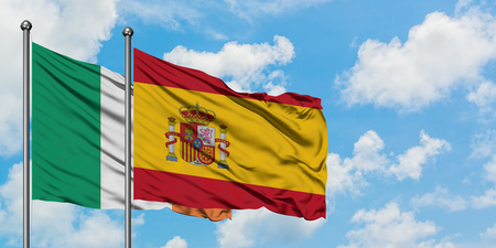 Ireland and Spain flag waving in the wind against white cloudy blue sky together. Diplomacy concept, international relations.