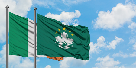 Ireland and Macao flag waving in the wind against white cloudy blue sky together. Diplomacy concept, international relations. Stock Photo