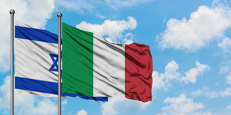 Israel and Italy flag waving in the wind against white cloudy blue sky together. Diplomacy concept, international relations.